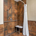 roll-in shower with seat, grab bars, and adjustable shower head